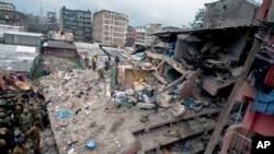 Polisi Kenya dan Anggota Layanan Pemuda Kenya mencari korban di lokasi runtuhnya bangunan di Nairobi, Kenya (30/4).