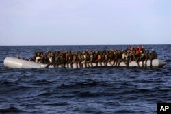 Sub-Saharan migrants crowd a rubber boat as they are rescued by members of Proactive Open Arms NGO, in the Mediterranean Sea, about 22 miles north of Zumarah, Libya, Jan. 27, 2017. Italy's coast guard, meanwhile, says it picked up about 1,000 migrants.