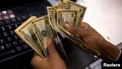 Un cajero cuenta las ganancias en un almacen de Nueva York. Los ejececutivos de las grandes empresas están levemente optimistas de que mejore la economía.