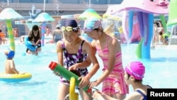FILE - Visitors cool off at Munsu Water Park east of Pyongyang, North Korea — a project in which wealthy individuals known as Donju are said to have played a key role.