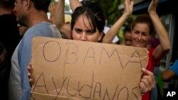 Una migrante cubana varada en Costa Rica muestra un cartel pidiendo ayuda al presidente de EE.UU. durante una protesta en noviembre de 2015. Países centroamericanos aprobaron un plan para ayudar a los migrantes a llegar a EE.UU. por vía aérea y terrestre.