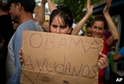 Una inmigrante cubana pide ayuda al presidente Barack Obama durante una protesta en Nicaragua. Nov. 16, 2015.