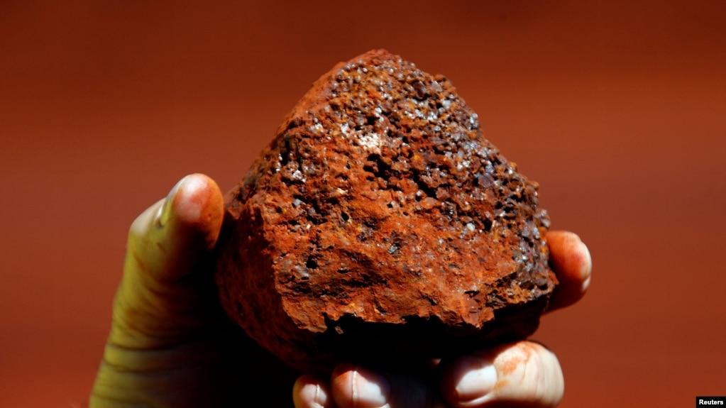 资料照:一名澳大利亚矿工手握澳西部地区产出的一块铁矿石。