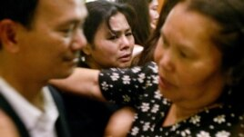Chen Kasanoy, center, watches as her husband, Mike Bunthung, left greets and comforts family members and friends at the funeral for their slain son Woodtee Bunthung Sunday, Jan. 11, 2004, in Long Beach, Calif. Six young Cambodian-American men, including a Marine just back from Iraq, have died since late October in a rash of suspected gang-related violence in Long Beach, home to the largest concentration of Cambodians outside Phnom Penh. Police say at least three of thevictims had gang affiliations; the others may have been cases of mistaken identity. (AP Photo/Ric Francis)