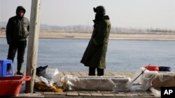 中国渔民在丹东的河边卖鱼,河对岸是朝鲜边境城镇新义州。(2013年2月7日)