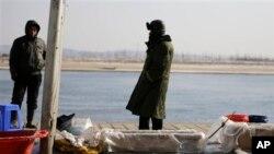 中国渔民在丹东的河边卖鱼,河对岸是朝鲜边境城镇新义州