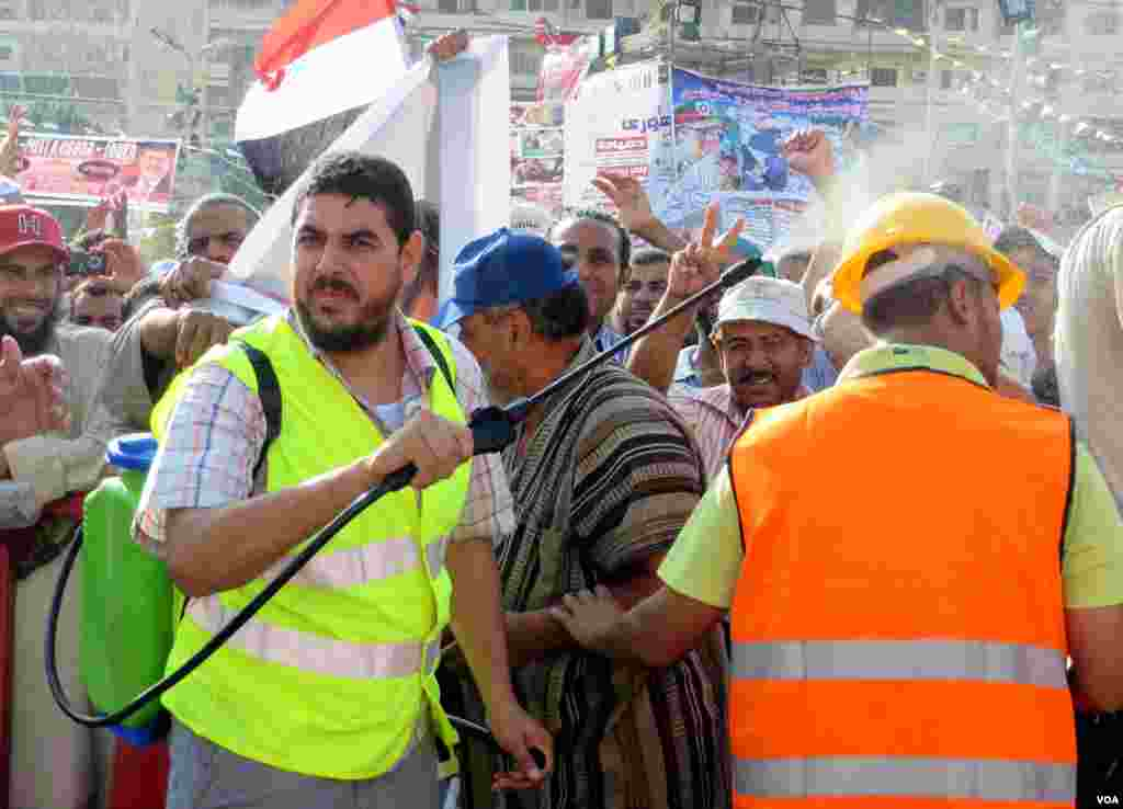 Hava çox isti olduğuna görə oruc tutan Mursi tərəfdarları üzərlərinə su tökür
