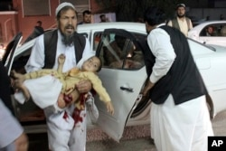 A man carries a wounded boy to a hospital after a car bombing outside a sports stadium in Lashkargah, capital city of southern Helmand province, Afghanistan, March 23, 2018. Provincial chief of police Abdul Ghafar Safi said the blast was carried out by a suicide bomber and that the target was civilians.