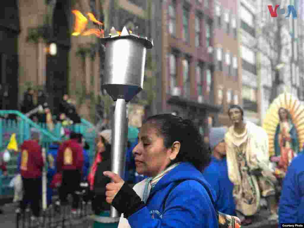 Una señora sostiene una torcha mientras camina en las calles de la Ciudad de Nueva York, rumbo a la Catedral de San Patricio. Foto: Celia Mendoza- VOA