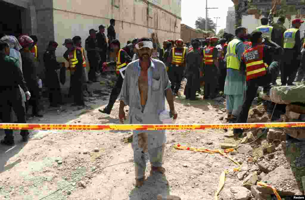 An injured man walks away as rescue workers search after a blast near the residence of the home minister of Punjab province, Shuja Khanzada, in Attock, Pakistan.The bomb killed Khanzada and at least eight others when it destroyed the minister's home, rescue officials said.