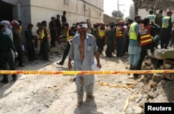 FILE - An injured man walks away as rescue workers search after a blast near the home of the home minister of Punjab province, Shuja Khanzada, in Attock, Pakistan, Aug. 16, 2015.