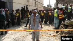 Seorang pria yang terluka menjauh saat saat para petugas membantu pencarian para korban serangan bom di Shuja Khanzada, provinsi Punjab, Atok, Pakistan, 16 Agustus 2015 (Foto: dok).