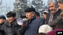 Sotsial-Demokratik partiya hamraisi Jarmaxan Tuyakbay Almatidagi namoyishda so'zlamoqda, 28-yanvar, 2012-yil. Mitingda parlament saylovlari natijalari va Janao'zenda konchilar isyonining kuch bilan bostirilganini tanqid qilindi. Yig'in huquq-tartibot xodi