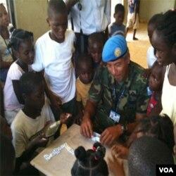 Kolonèl Victor Nuñez ap jwe domino ak kèk timoun nan yon òfelina ki rele « Centre Chretien de l' Enfant Haitien » nan Delmas 65