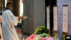 Seorang pendeta Katholik tengah menyiramkan air suci ke tempat peringatan untuk mengenang korban pembunuhan massal di kompleks Resorts World Manila, di Manila, Filipina, 2 Juni 2017. (Foto: dok). Pemerintah Filipina sedang mempersiapkan proses ekstradisi seorang pendeta Katolik Filipina yang menghadapi tuduhan melakukan pelecehan seksual terhadap dua anak laki-laki di dua gereja diNorth Dakotapada 1990-an.