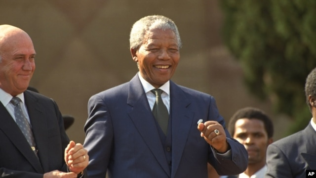 FILE - President Nelson Mandela dances at a celebration concert following his inauguration at the Union Buildings in Pretoria, South Africa, May 10, 1994.