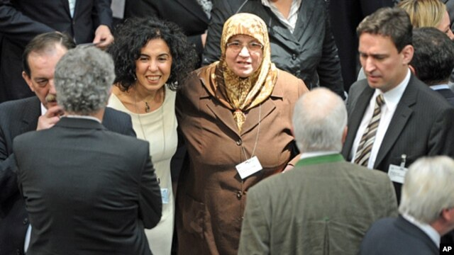 Electoral delegate for the Christian Democratic Party (CDU) Mevluede Genc, center, a German of Turkish origin, stands with other delegates in the Reichstag in Berlin,  March 18, 2012.