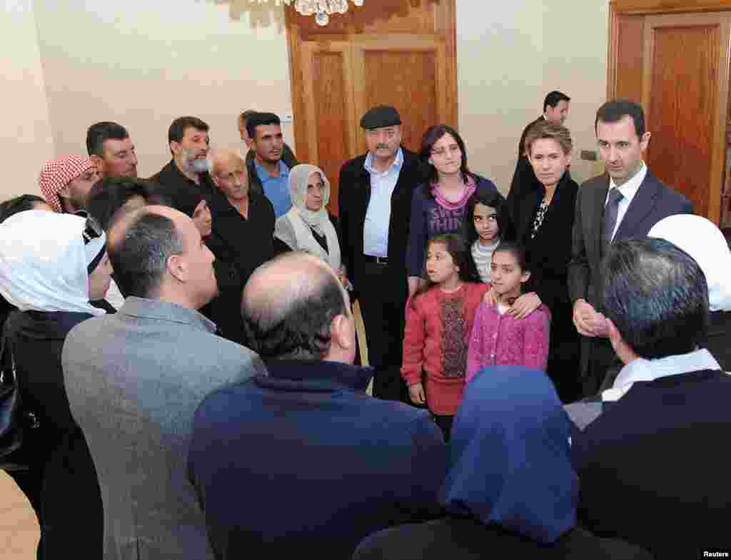 Syrian President Bashar al-Assad and his wife Asma visit families of students killed during clashes between forces loyal to him and their opponents in Damascus in this handout photograph released by Syria's national news agency SANA on March 20, 2013.