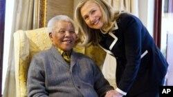 La secretaria de Estado de EE.UU, Hillary Clinton, y el ex residente Mandela posan sonrientes para los fotógrafos.