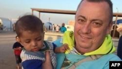 Trong bức ảnh do Văn phòng Đối ngoại và Khối thịnh vượng chung của Anh cung cấp, nhân viên cứu trợ người Anh Alan Henning đang bế một em bé ở trại tỵ nạn tại biên giới Thổ Nhĩ Kỳ và Syria.
