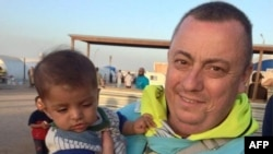 A handout image received from Britain's Foreign and Commonwealth Office on Sept.15, 2014 shows British aid worker Alan Henning holding a child in a refugee camp on the Turkish-Syrian border.