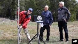 El gobernador de California, Jerry Brown (centro) observa hasta donde debería estar la nieve en las montañas de la Sierra Nevada.