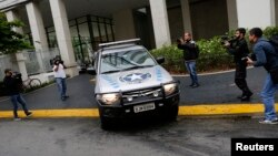 "Members of the media record as a vehicle belonging to the Brazilian Federal Revenue Authority (RFP) leave the headquarters of Brazilian conglomerate Camargo Correa during ""Operation Car Wash"" in Sao Paulo, Nov. 14, 2014."
