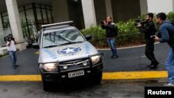 "FILE- A vehicle belonging to the Brazilian Federal Revenue Authority leaves the headquarters of Brazilian conglomerate Camargo Correa during ""Operation Carwash"" in Sao Paulo, Nov. 14, 2014. Fifteen search warrants in the ""Operation Carwash"" probe were issued Wednesday."