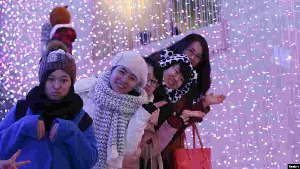 Des touristes posent pour une photo devant des illuminations de Noël. Pékin, 23 décembre 2014.