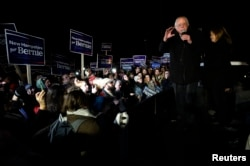 U.S. Democratic presidential candidate Bernie Sanders, with his wife Jane, addressess supporters from the bed of a pickup truck after arriving early morning in Bow, New Hampshire from Iowa Feb. 2, 2016.