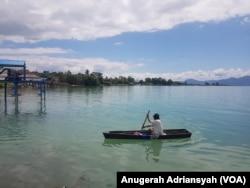 Seorang warga kecamatan Nainggolan, Pulau Samosir tengah mengayuh sampan di Danau Toba, Sumatera Utara. (Foto: VOA/Anugerah Adriansyah)