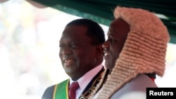 Zimbabwe's President Emmerson Mnangagwa is congratulated by the Chief Justice, Luke Malaba, after taking the oath of office during his presidential inauguration ceremony in Harare, Aug. 26, 2018.