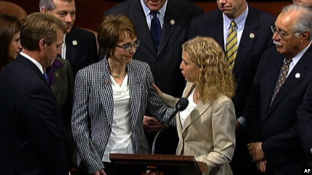 This video image provided by House Television shows Rep. Gabrielle Giffords, D-Ariz., accompanied by Democratic National Committee Chair Rep. Debbie Wasserman Schultz, D-Fla., walks  on the floor of the House on Capitol Hill in Washington, Wednesday, Jan.