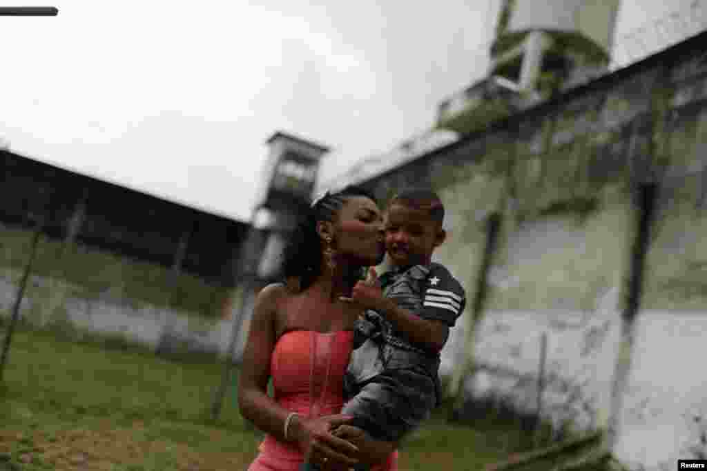 "A prisoner and participant of the ""TB Girl"" beauty contest holds her son at the Talavera Bruce women prison in Rio de Janeiro, Brazil."