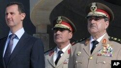 Chapdan prezident Bashar al-Assad, kimligi noma'lum harbiy va o'ngda, bugungi portlashda halok bo'lgan Mudofaa vaziri Dovud Rajha