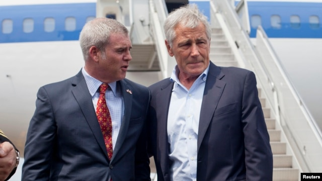U.S. Defense Secretary Chuck Hagel (R) is greeted by U.S. Ambassador to Singapore Kirk Wagar upon arriving in Singapore May 30, 2014.