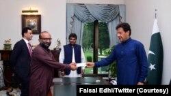 وزیر اعظم عمران خان ایدھی فاؤنڈیشن کے فیصل ایدھی سے چیک وصول کر رہے ہیں۔ (فائل فوٹو)