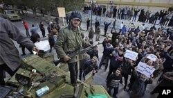 무장한 반군 중 한 명이 정규군으로부터 빼앗은 탱크 위에 서 있다.