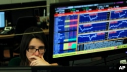 A broker works in a trading room of a Portuguese bank in Lisbon, Wednesday, July 3, 2013.