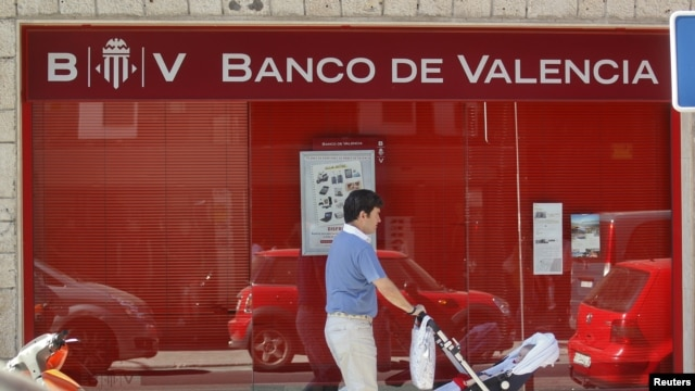 A man pushes a pram past a Banco de Valencia bank branch in Madrid, June 25, 2012.