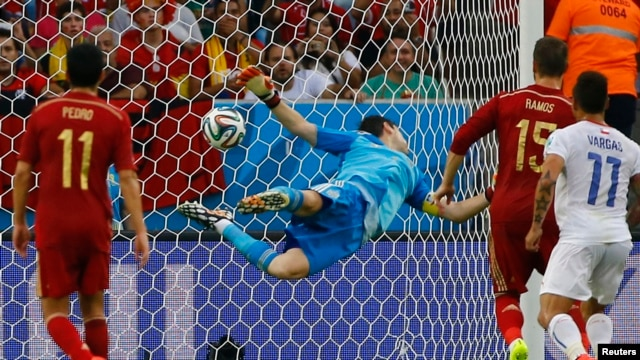 Spain's goalkeeper Iker Casillas dives trying to save a ball from Chile's Charles Aranguiz (not pictured) during their 2014 World Cup Group B soccer match at the Maracana stadium in Rio de Janeiro, June 18, 2014.