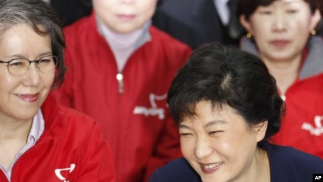 Park Geun-hye (R), interim leader of the ruling Saenuri Party, and party members smile as they watch a television report on an exit poll of the parliament elections at the party's headquarters in Seoul, April 11, 2012.