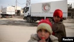 Children stand along a street as an aid convoy of Syrian Arab Red Crescent and United Nation (UN) drives through the rebel held besieged city of Douma towards the besieged town of Kafr Batna to deliver aid, on the outskirts of Damascus, Syria, Feb. 23, 2