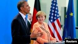 El presidente Barack Obama habla mientras la canciller alemana Angela Merkel escucha, durante la conferencia de prensa que siguió a la reunión entre ambos líderes en Berlín.