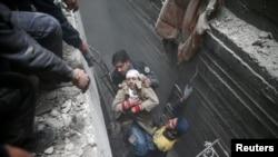 La défense civile syrienne aide une femme dans la ville assiégée de Douma, dans l'est de la Ghouta, à Damas, en Syrie, le 22 février 2018.