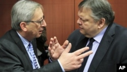 Luxembourg's Prime Minister and Eurogroup chairman, Jean-Claude Juncker (L) talks with Greece's Finance Minister Evangelos Venizelos at the start of a Eurogroup meeting at the European Union council headquarters in Brussels, February 9, 2012.