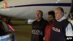 Foto yang dirilis oleh kepolisian Italia ini menunjukkan gambar Yehdego Mered (35 tahun, berkaos merah), warga Eritera yang diduga mendalangi jaringan penyelundup migran ke Italia diekstradisi dari Sudan ke Italia (8/6).