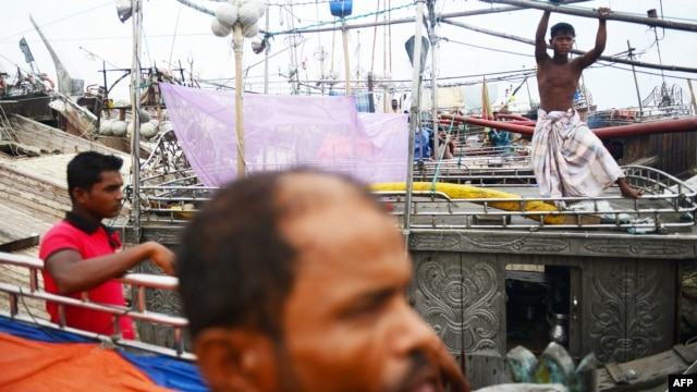 Bangladeshi fishermen tie up their vessels in the harbor of Chittagong during preparations for the expected arrival of Cyclone Mahasen, May 15, 2013.