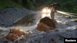 FILE - In early July, flooding struck southwestern Japan, including Hita, in Oita Prefecture, where a flooded road with fallen rocks is pictured, July 5, 2017. In northeast Japan, tens of thousands have been told to evacuate because of heavy rain and flooding.