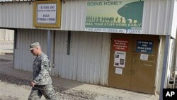 A U.S. Army soldier walks under a post office sign at Camp Victory near Baghdad, Iraq, October 15, 2011.